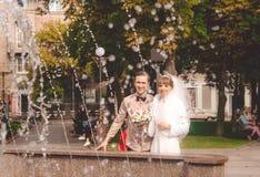 笑的新娘和新郎以城市喷泉为背景 库存照片