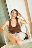 笑的松弛大阳台妇女 免版税库存图片