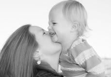 笑的母亲和孩子,拥抱和 免版税库存图片