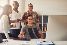 笑的男人和妇女计算机的在办公室 图库摄影