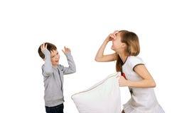 笑的男孩和女孩战斗的枕头 免版税库存照片