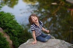 笑的男孩坐冰砾在池塘 免版税库存图片