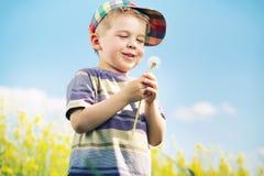 笑的男孩运载的絮球在他的手上 免版税库存照片