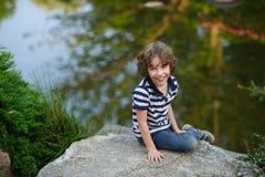 笑的男孩,当坐湖边时 库存图片