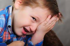 笑的男孩画象关闭他的眼睛手 库存照片
