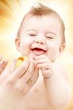 笑的男婴在有橡胶鸭子的母亲手上 免版税库存照片