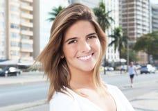 笑的白肤金发的妇女在城市 免版税库存图片