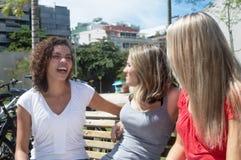 笑的西班牙妇女谈话与白种人girlfirend 免版税库存照片