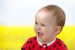 笑的逗人喜爱的女婴在夏天 免版税库存照片