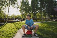 笑的青少年的男孩坐一辆小玩具汽车在乡下在一个晴朗的夏天晚上 在背景中有桦树 免版税库存照片