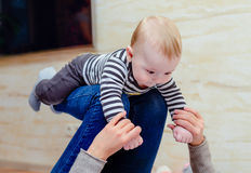 嘻嘻笑的婴孩成人膝盖的  免版税库存图片