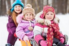 笑的更老的女孩推挤两个女孩坐的sledgesin 库存图片