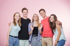 笑站立愉快的微笑的年轻的小组的朋友一起谈话和 最好的朋友 免版税库存照片