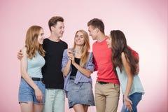 笑站立愉快的微笑的年轻的小组的朋友一起谈话和 最好的朋友 图库摄影