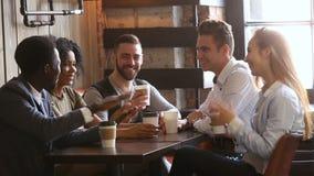 笑给的不同种族的年轻朋友高五在会议上在咖啡馆 股票视频