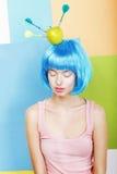 笑话。在蓝色假发的异常妇女穿着或行为古怪的人与箭和绿色苹果计算机 库存图片