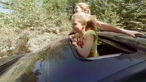 笑飞跃在汽车的舱口盖的外面两个愉快的年轻金发碧眼的女人在活动中反对森林 股票录像