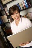 笑高级常设妇女的膝上型计算机 免版税库存照片