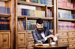 笑,放松,乐趣,休闲,爱好概念 愉快的人在内部的葡萄酒坐并且享受松弛读书 博若莱红葡萄酒 免版税库存照片
