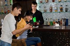笑年轻的夫妇,他们喝在酒吧 库存照片