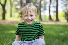 笑年轻的男孩,当坐在草在公园时 库存图片