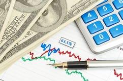 笔、在图表特写镜头的计算器和美元 库存图片