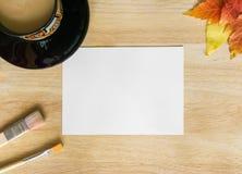 画笔、秋叶、黑咖啡和在木桌上的白皮书 免版税库存照片