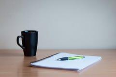 笔、笔记本和杯子 免版税库存图片