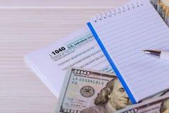 笔、笔记本和美金是在报税表1040 U的谎言 S 单独收入税单 免版税图库摄影