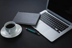 笔、组织者、无奶咖啡和膝上型计算机在黑背景 库存图片