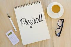 笔、计算器、玻璃、acup咖啡和笔记本顶视图写与工资单在木背景 库存照片