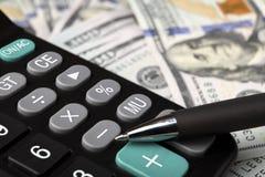 笔、计算器和金钱美元在桌上 特写镜头 免版税库存图片
