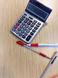 笔、铅笔和计算器木表面上 库存图片