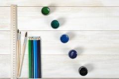 画笔和厘米统治者顶视图与五颜六色的树胶水彩画颜料容器在木背景 图库摄影