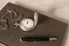 笔和时钟在书 免版税库存照片