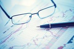 笔和玻璃在财政图 免版税库存照片