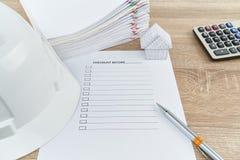 笔和白色工程师帽子有清单的在木桌上 库存图片
