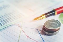 笔和硬币在工商业票据 报告图 免版税库存照片