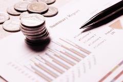 笔和硬币在综合报告与纸图在书桌上 库存照片
