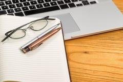 笔和空白的笔记薄与计算机在桌面上 库存图片