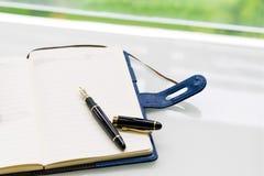 笔和笔记本在白色桌上在窗口, sideview附近有绿色背景 库存图片