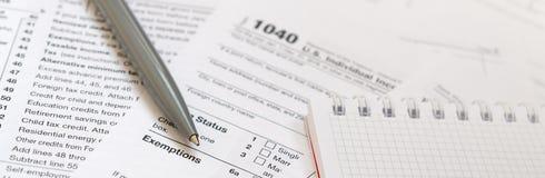 笔和笔记本是在报税表1040 U的谎言 S Individua 免版税库存照片