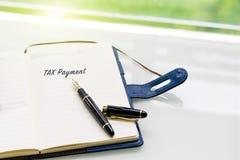笔和笔记本有付税词的在白色桌上在窗口, sideview附近有绿灯背景 库存图片