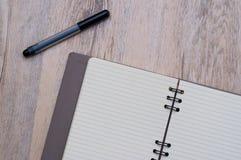 笔和笔记本,在木纹理 黑笔和笔记本日志 库存图片