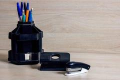 笔和铅笔在立场、订书机和打孔器 库存照片