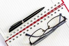 笔和镜片在笔记本 免版税库存照片