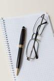 黑笔和玻璃与白色垫或笔记薄 免版税库存照片