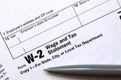 笔在报税表W-2薪水和税声明说谎 蒂姆 图库摄影
