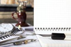 笔的老笔杆和减速火箭的指南针在开放笔记本说谎 在笔的技巧的锋利 特写镜头 免版税库存图片