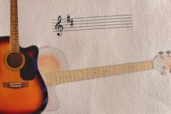 笔记和音响镶有钻石的旭日形首饰的吉他在概略的纸板背景的左边 免版税库存图片